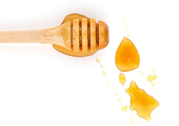 Мед капает из деревянного ковша на белой изолированной поверхности