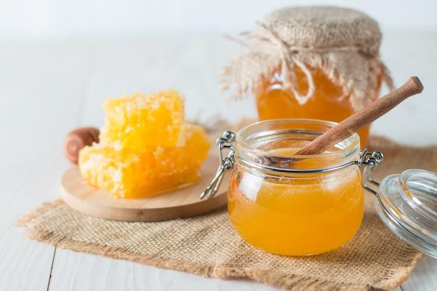 素朴な木製の灰色の瓶に木製の蜂蜜ディッパーから滴り落ちる蜂蜜