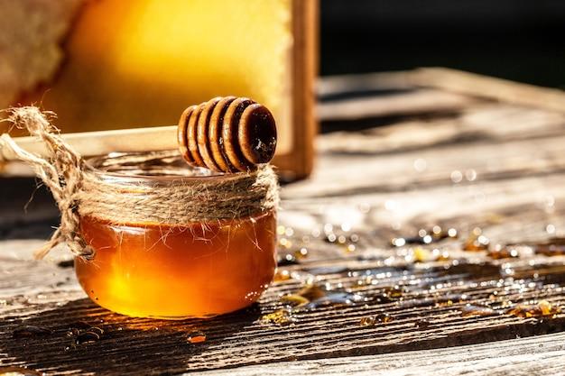 Мед капает из деревянной ковши для меда в банке на деревянном деревенском фоне