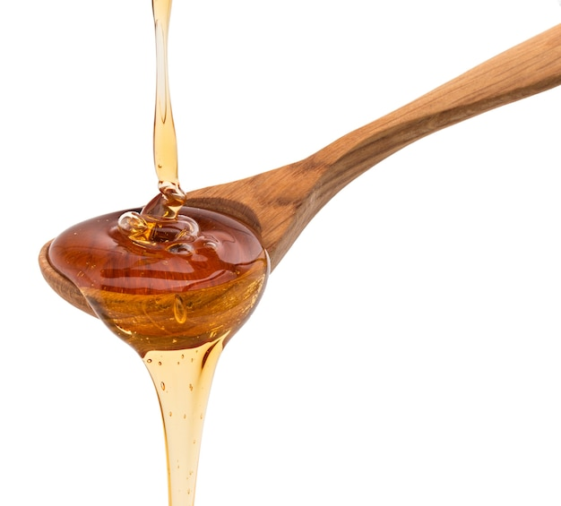 꿀 흰색 배경에 컷 아웃에 고립 된 나무 꿀 디퍼에서 떨어지는