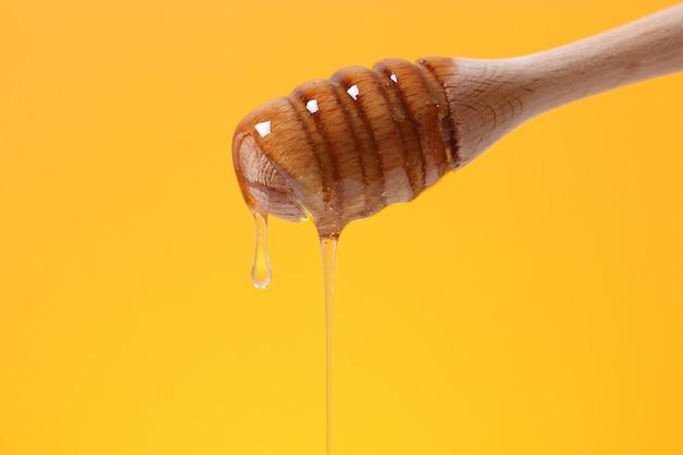 Мед капает из деревянной ложки для меда на цветном ярком фоне