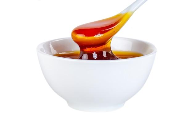 Мед капает из керамической ложки в керамическую миску, еда