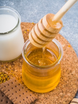 Honey dripping from dripper in glass pot with milk and biscuits on cork coaster