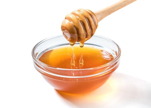 꿀 흰색 표면에 꿀 디퍼에서 떨어지는. 나무 꿀 숟가락에서 담그는 두꺼운 꿀. 건강 식품 개념.