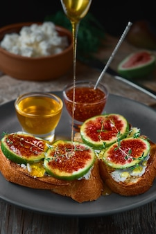 Honey dripping from a spoon onto fig sandwiches on toasted goat cheese baguette on a plate with honey