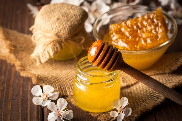 Honey dripping from a wooden honey dipper in a jar on wooden grey rustic