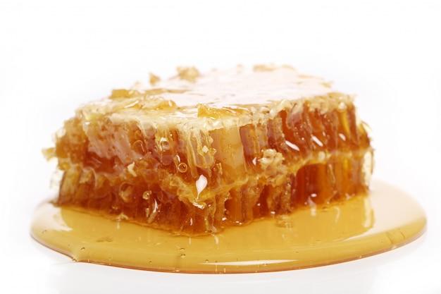 Miele gocciolante da un cucchiaio di legno