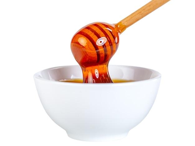 Мед капает из деревянного ковша в керамическую миску, еда
