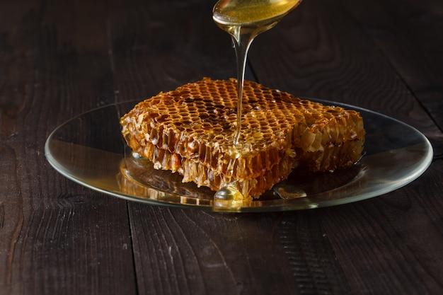 蜂蜜、木製の灰色の素朴なテーブルのプレートに滴下