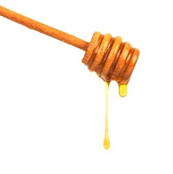 Капание меда изолированное на белом космосе. мед изолированный