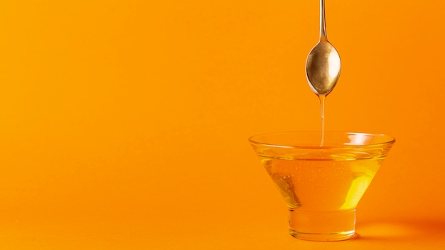 Honey dripping off spoon in bowl with copy space