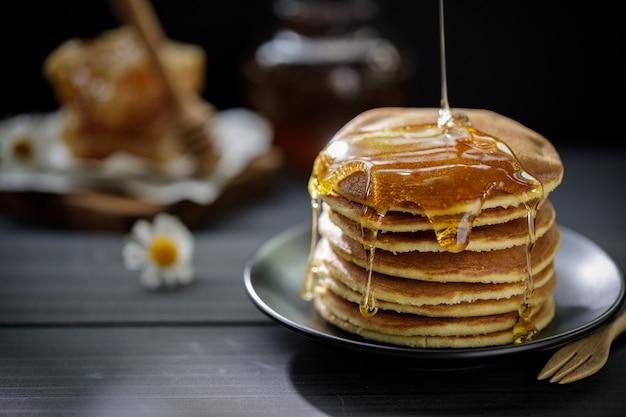 나무 테이블에 아침 팬케이크의 스택에 떨어지는 꿀
