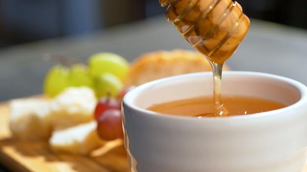 Мед капает, льется из ковша для меда в керамической миске