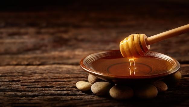 Мед капает из ковша для меда в миску. здоровый натуральный мед макают крупным планом деревянной ложкой меда