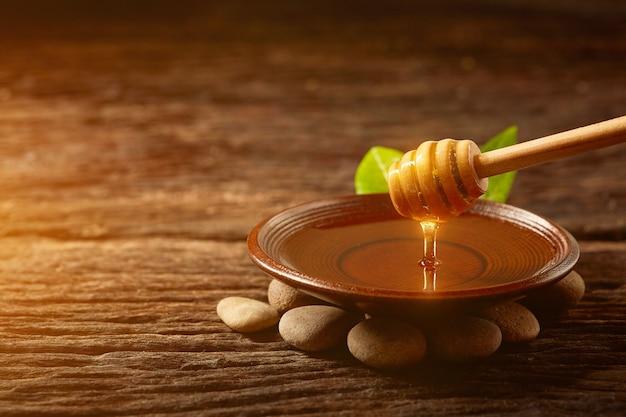 ボウルの中のハニーディッパーから蜂蜜が滴り落ちる。健康的な天然蜂蜜を浸したクローズアップ木のスプーン蜂蜜
