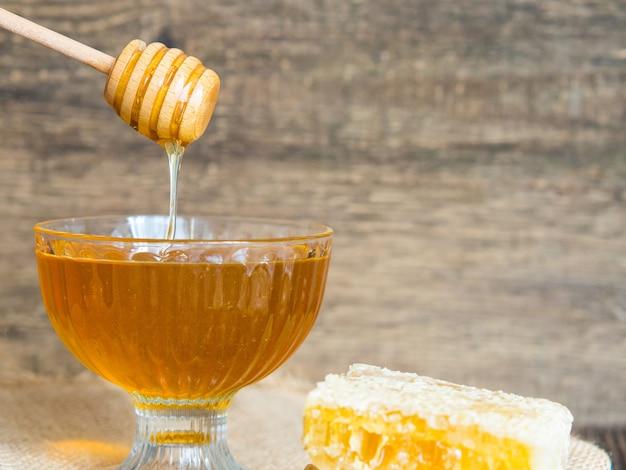 ハニーディッパーから美しいガラスのボウルに蜂蜜が滴り落ちる。閉じる。ヘルシーなオーガニックの濃厚なハチミツとコーム。