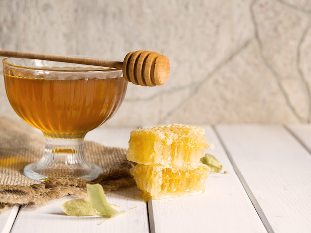 Honey drips from a honey dipper into a beautiful glass bowl. close-up. healthy organic thick honey and combs.