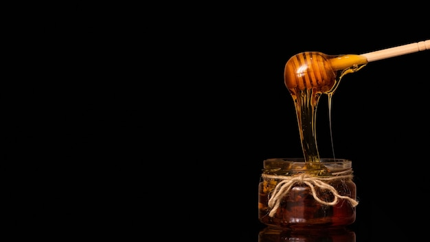 Honey drips from a spoon into a jar on a black background.