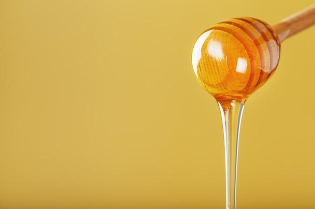 Мед тонкой струйкой капает из ковша для меда на желтом фоне.
