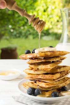 Honey falling on waffle tower