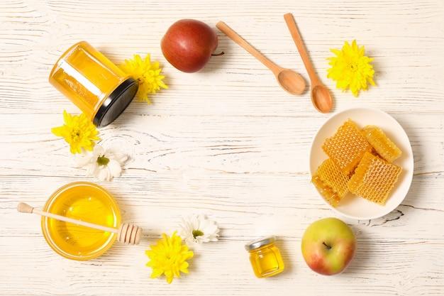 Мед, цветы и яблоки на белом фоне деревянные, копией пространства