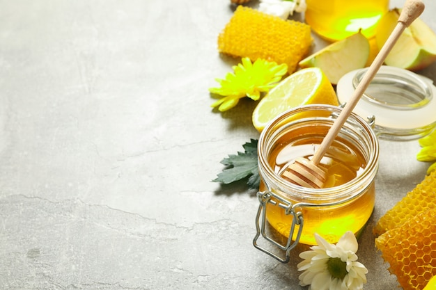 Honey, flowers and fruits on grey background, copy space