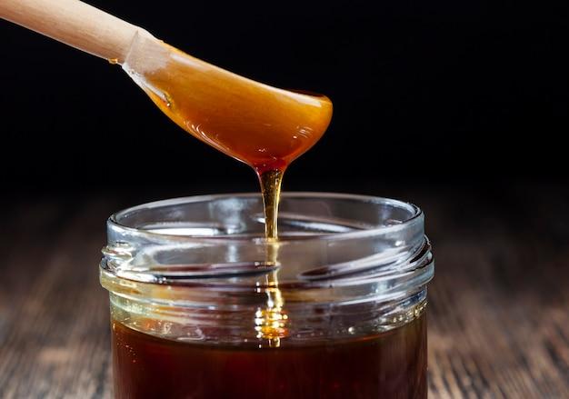 ガラスの瓶に流れ込む蜂蜜