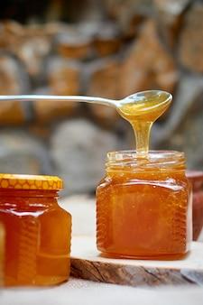 꿀은 강철 숟가락에서 유리 병으로 흐릅니다.