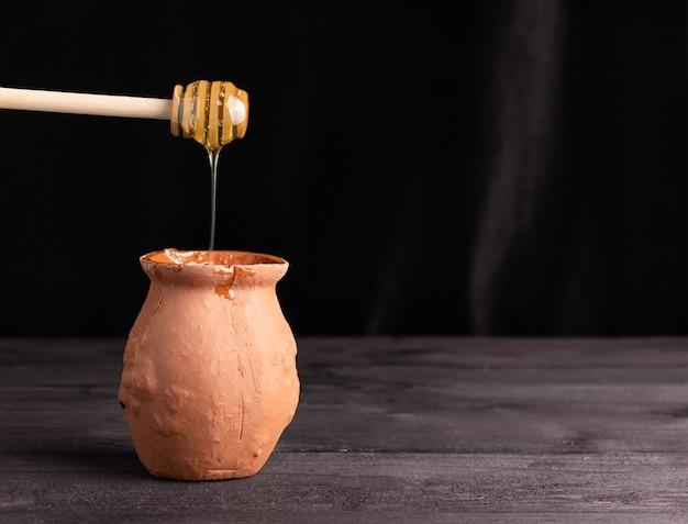 Мед льется из деревянной ложки в глиняный горшок, свободное место для текста. фермерство, пасека, здоровое питание.