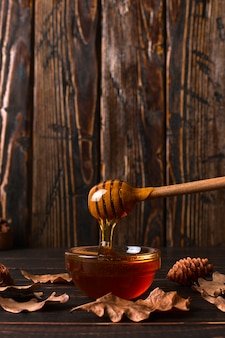 Honey flows from a stick into a jar. rustic sweet autumn photo, wooden background and dry leaves, copyspace.
