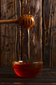 Honey flows from a stick into a jar. rustic sweet photo, wooden background, copyspace.
