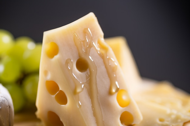 Honey flows over a piece of cheese