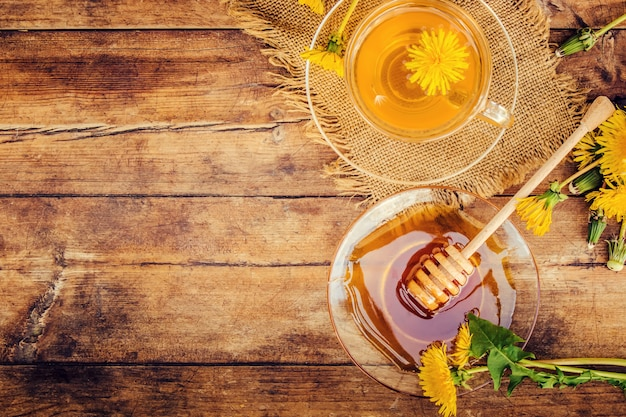Honey from dandelion and a cup of tea. selective focus.