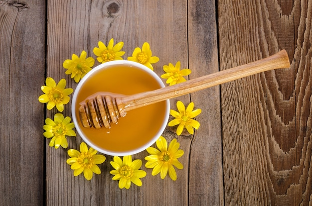 Honey in the glass bowl and yellow flowers around it
