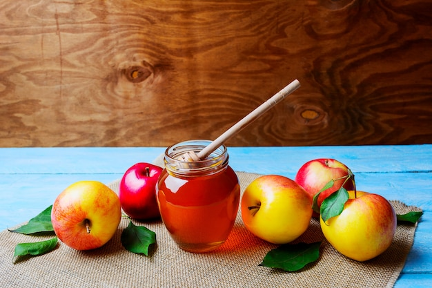 Honey glass jar and apples on rustic background copy space