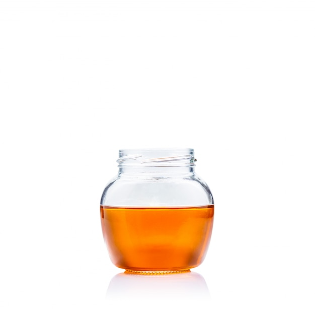 Honey in glass jar on white background with copy space