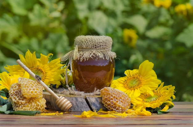 Honey in glass jar with bee flying