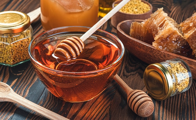 Honey in glass jar with honey dipper over wooden background with honeycomb and propolis, liquid sugar syrup, flower nectar