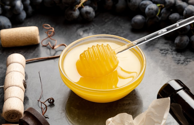 Honey in glass jar with honey spoon on dark stone board with wine cheese corkscrew black grapes. wine tasting with honey red wine cheese snacks on dark concrete background.