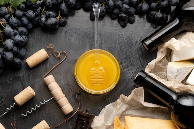 Honey in glass jar with honey spoon on dark stone board with wine cheese corkscrew in black juicy grapes frame. romantic dinner wine tasting with red wine cheese snacks on dark concrete background.