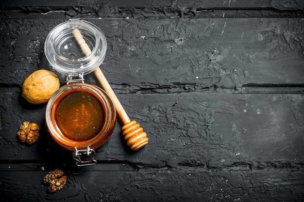 Honey in a glass jar with walnuts. on a black rustic.