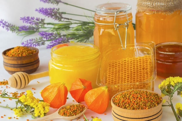 Honey in glass jars. honeycombs and pollen. flowers