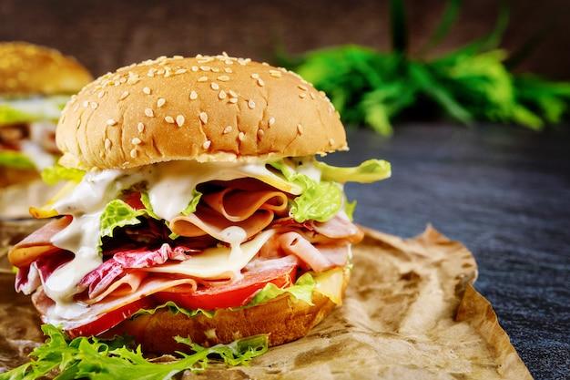 Медовый сэндвич с ветчиной, листьями салата, помидорами и сыром