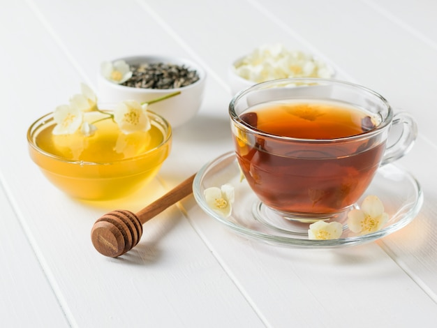 Honey, herbal tea and jasmine on a white wooden table. a set of natural products for the treatment of many diseases.