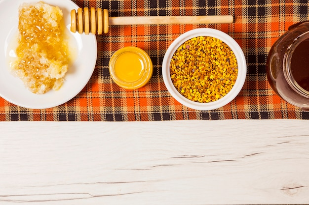 Honey; honeycomb and bee pollen arranged in a row on table cloth