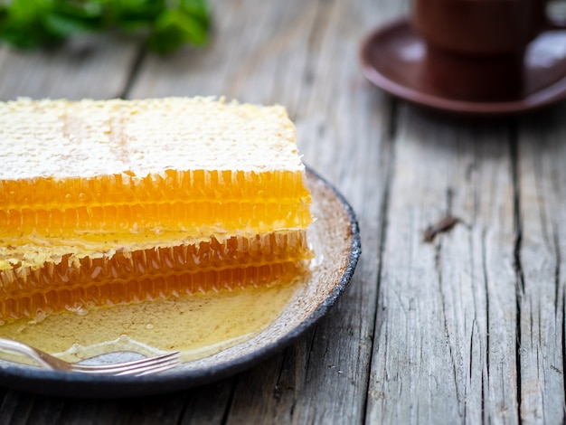 Honey in honeycomb, close-up, on ceramic plate, on wooden rustic