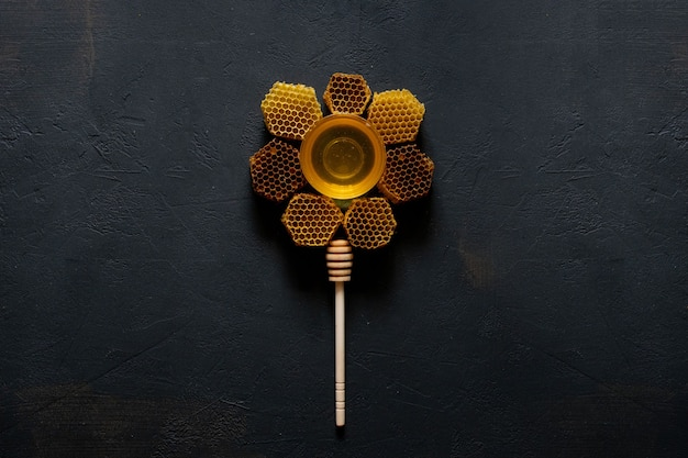Honey and honeycomb in the form of a flower on black table