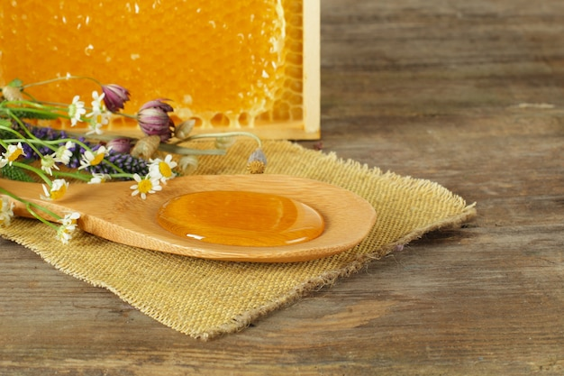 Honey and honeycomb with summer flowers,