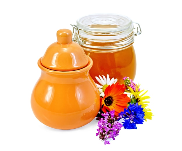 粘土の水差しと白い背景で隔離の花とガラスの瓶の蜂蜜