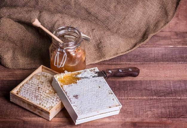 ガラスの瓶の中の蜂蜜と木製の背景にナイフで蜂蜜